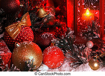 balls and Christmas bell are covered with snow in the light of a red lantern on the background of New Year's scenery