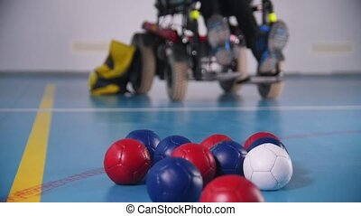 Balls for boccia. Tricolor. A disabled man throwing them....