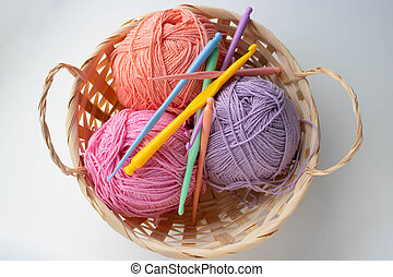 Balls of colored yarn in a basket on white background