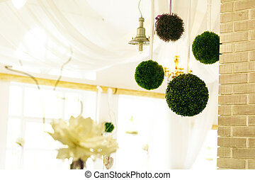 Balls of greenery hang on a ceiling in the restaurant