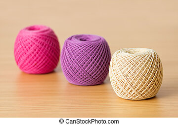 Balls of threads on a wooden table