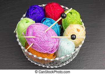 balls of wool in a basket with knitting needles