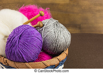 balls of wool in basket with knitting needles