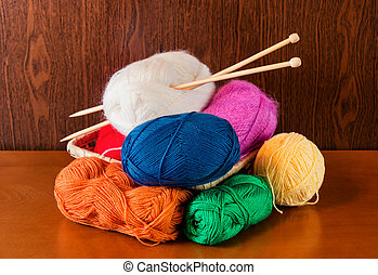 Balls of yarn in basket with knitting needles. Selective focus