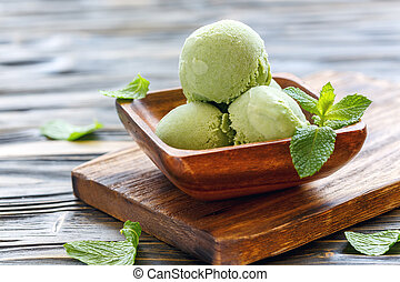 Balls with mint ice cream in a wooden bowl.