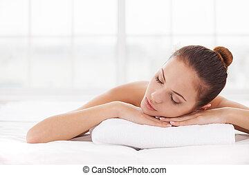 balneario, woman., hermoso, mujer joven, mantener, ojos cerrados, mientras, acostado, en, tabla del masaje