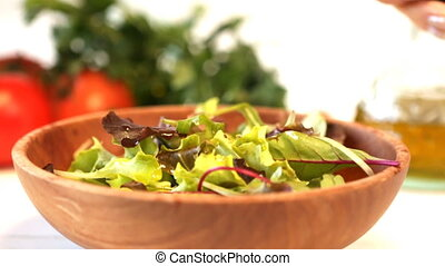 Balsamic vinegar dressing being poured over healthy salad...