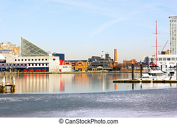 Baltimore Inner Harbor in winter. Buildings reflections in icy waters.
