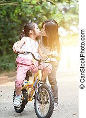 bambino, bicicletta cavalca, e, dare, bacio, a, madre, esterno, park.