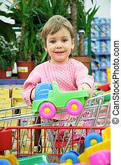 bambino, in, shoppingcart, con, automobile gioco