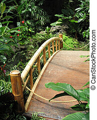 A vertical shot of a bamboo bridge in a tropical setting