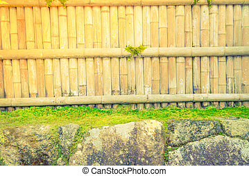 Bamboo fence on stone with green leaves . ( Filtered image...