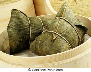 Steamed Chinese rice dumplings (zongzi) wrapped in bamboo leaves, filled with glutionous/sticky rice, pork, mushrooms, and peanuts. These are eaten during the Dragon Boat Festival.