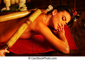 Bamboo massage of woman in spa salon. Interior oriental therapy .
