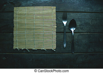 bamboo mat spoon and fork on brown wooden surface