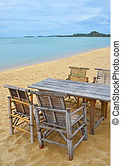 Bamboo table and chairs on sand beach
