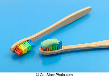 Bamboo toothbrush with green toothpaste on blue background with water drops