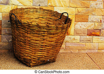 Bamboo trash basket with a stone background.