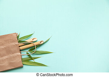 Bamboo trunks and lieaves in paper bag on azure background. ...