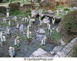 Bamboos filled with candles in a small river in front of a waterfall