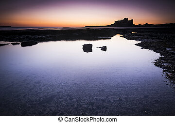 Bamburgh castle in Northumberland seen across rockpools at dawn