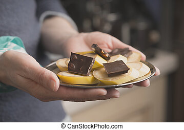 Banana and chocolate slices on the plate in the hand horizontal