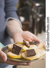 Banana and chocolate slices on the plate in the hand vertical