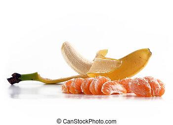 Banana and tangerine slices. Fresh fruit over white
