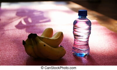 Banana and water bottle on exercise mat at home 4k -...