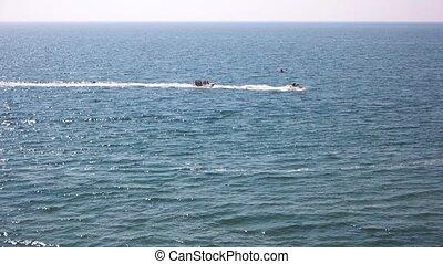 Banana boat ride, sea. Jet ski in the distance.