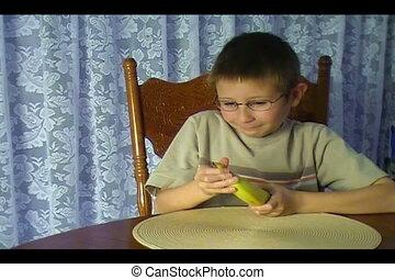 Banana Boy - Young boy peeling and eating a banana