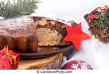 Banana cake bread traditional pie on snow surfase for Christmas dessert table. Christmas New Year decorations.