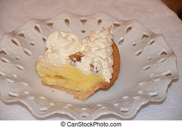 Banana Cream Pie - A slice of banana cream pie on a white...