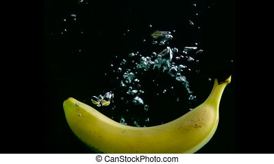 Banana falls in the water in slow motion. Isolated on black background with alpha. Close up view