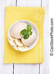 Banana ice cream in bowl, top view - Scoop of banana ice...