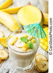 banana mango smoothie on a white wood background. toning....