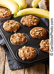 Banana nut muffins close-up in a baking dish. vertical