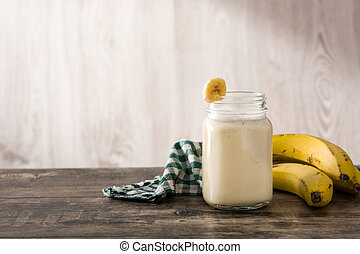 Banana smoothie in jar on wooden table. Copy space