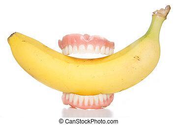 banana teeth - Smiling banana false teeth biting into health