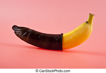 Banana with a black condom on a pink background. Safe sex concept
