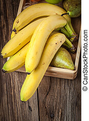 Bananas and other fruits in a wooden box.