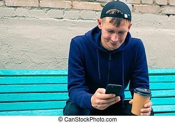 banco, homem, bebendo, jovem, parque, madeira, café, seu, telefone, uso, sentando