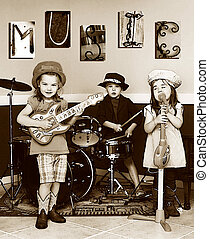 Three siblings pretend to be a music band. They are playing instruments and one is singing. The letters M, U, S, I, C is posted on the wall. Youngest member is singing.
