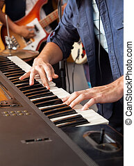 Midsection of male band member playing piano in recording studio