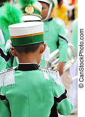 Young band member in a green uniform before a performance