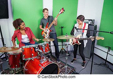 Band Members Performing In Recording Studio