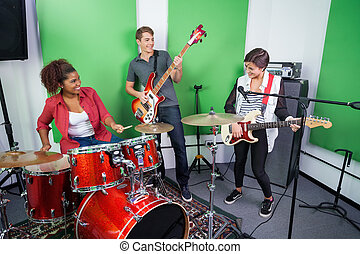Band Members Performing In Recording Studio