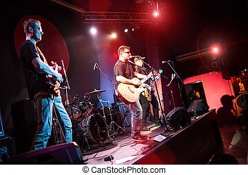 Band performs on stage in a nightclub
