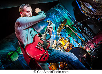 Band performs on stage, rock music concert. Warning - Focus...