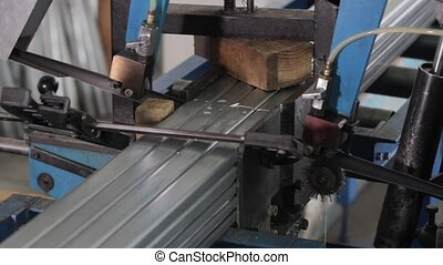 Band saw saws a stack of metal profiles for the production...